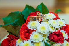 Two gold wedding rings lie on a bouquet with white flowers and red roses. Stock Photo