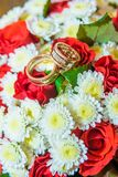 Two gold wedding rings lie on a bouquet with white flowers and red roses. Stock Photos