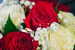 Two gold wedding rings lie on the bridal bouquet composed of white and red roses stock image