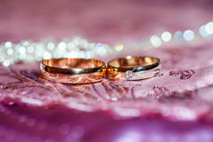 Two gold wedding rings lie on a pillow Royalty Free Stock Image