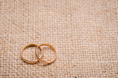 Two gold wedding rings. Lying on brown cloth sacking Royalty Free Stock Photos