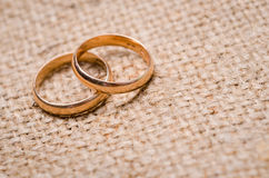 Two gold wedding rings. Lying on brown cloth sacking Royalty Free Stock Image