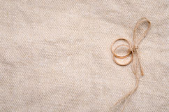 Two gold wedding rings. Lying on brown cloth sacking Stock Images