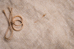 Two gold wedding rings. Lying on brown cloth sacking Royalty Free Stock Photo