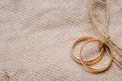 Two gold wedding rings. Lying on brown cloth sacking Royalty Free Stock Images
