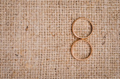 Two gold wedding rings. Lying on brown cloth sacking Stock Photos