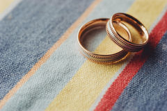 Two gold wedding rings lying on colored cloth. Golden wedding rings lying on colored textile Royalty Free Stock Images