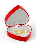 Two gold wedding rings lying in a red heart-shaped box. Stock Images