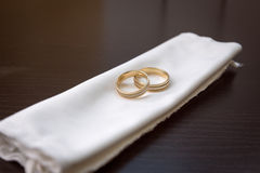 Two gold wedding rings lying on a white cloth on a dark background. Two gold wedding rings lying on a white cloth Stock Photo