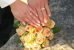Two gold wedding rings on roses bouquet. Two gold wedding rings on pink and yellow roses bouquet Royalty Free Stock Images