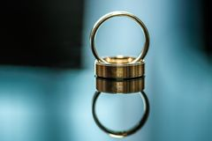 Two wedding rings on shiny surface. Two gold wedding rings on shiny blue surface with blurred background Royalty Free Stock Image