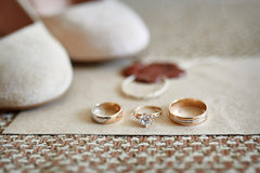 Two gold wedding rings and shoes of bride on background Stock Images