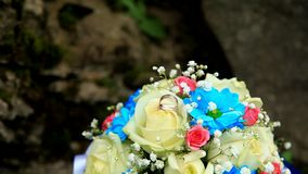 Two gold wedding rings on the wedding bouquet. Background stock video