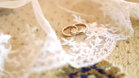 Two gold wedding rings on a white veil of the bride.Two wedding rings on a veil.Wedding gold rings on the veil. Wedding stock video