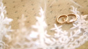 Two gold wedding rings on a white veil of the bride.Two wedding rings on a veil.Wedding gold rings on the veil. stock video footage
