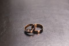 Two gold wide wedding rings, located on a surface of brown leather stock photo
