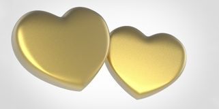 Two gold yellow 3D Hearts on white gray grey background Royalty Free Stock Photos