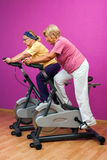 Two golden agers doing spinning in gym. Royalty Free Stock Photo