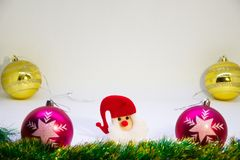 Two golden balls, two pink balls, with Santa in a red hat in the middle with Christmas decorations. Festive, Christmas card,two pink balls,two golden balls Royalty Free Stock Image