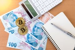 Two golden bitcoins, calculator, journal and pen on turkish liras Royalty Free Stock Images