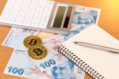 Two golden bitcoins, calculator, journal and pen on turkish pape Stock Photography