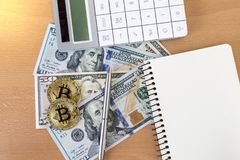 Two golden bitcoins, journal, pen, and calculator on us dollars. Top view stock images