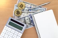 Two golden bitcoins, journal, pen, and calculator on us dollars. Top view royalty free stock photo