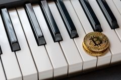 Two golden bitcoins on the keyboards of the piano. Close-up Royalty Free Stock Images