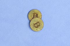 Two golden bitcoins lies on a blanket made of soft and fluffy light blue fleece fabric. Physical visualization of virtual crypto c. Urrency Stock Photography