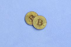 Two golden bitcoins lies on a blanket made of soft and fluffy light blue fleece fabric. Physical visualization of virtual crypto c. Urrency Royalty Free Stock Images