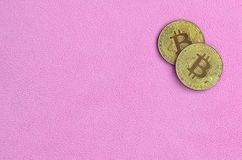 Two golden bitcoins lies on a blanket made of soft and fluffy light pink fleece fabric. Physical visualization of virtual crypto c. Urrency Stock Photos