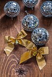 Two golden bows and christmas disco mirror balls on old wooden b Stock Photos