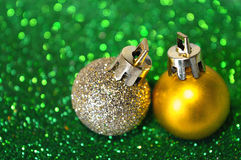 Two golden Christmas balls on blurry background of green glitter Stock Photo