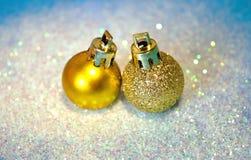 Two golden Christmas balls on white glitter on blue background Stock Photo