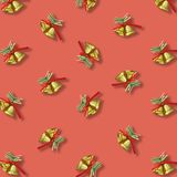Two golden christmas bells with a red ribbon bow pattern on red royalty free stock photography