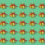 Two golden christmas bells with a red ribbon bow pattern on gree stock image