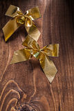 Two golden christmas boaws with small bells on old brown wooden Stock Photo