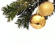 Two golden Christmas decorations hanging from a tree
