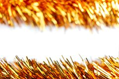 Two golden Christmas tinsels. Isolated on white background royalty free stock photo