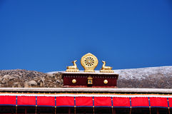 Two golden deer flanking a Dharma wheel on Drepung Monastery. The rooftop statues of two golden deer flanking a Dharma wheel on Drepung Monastery main building royalty free stock photo