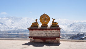 Two golden deer flanking a Dharma wheel on Drepung Monastery. The rooftop statues of two golden deer flanking a Dharma wheel on Drepung Monastery main building royalty free stock images