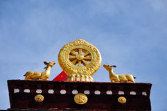 Two golden deer flanking a Dharma wheel on Jokhang. The rooftop statues of two golden deer flanking a Dharma wheel on the Jokhang.The Jokhang , also called the royalty free stock image