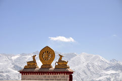 Two golden deer flanking a Dharma wheel and snow mountain Stock Photography