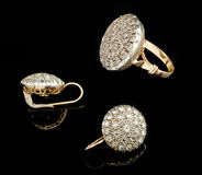 Two golden earrings and ring with diamonds Stock Photos