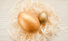 Two golden easter eggs in white nest decoration Stock Photos
