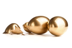 Two Golden Eggs Near The Broken Egg Stock Image