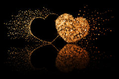 Two golden hearts on black background with reflection effect Stock Photos