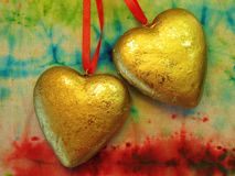 Two golden hearts on colorful background Royalty Free Stock Photos
