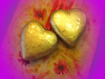 Two golden hearts. On purple background royalty free stock photography