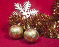 Two golden New Year's balls and ribbon on a red background Stock Images